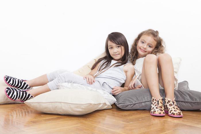bunte hausschuhe für kinder, kleine mädchen, die auf kissen sitzen