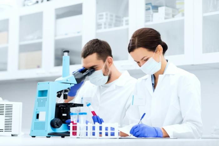 zwei junge Laboranten, Chemielabor, Kolben, Mikroskop, wissenschaftlicher Fortschritt