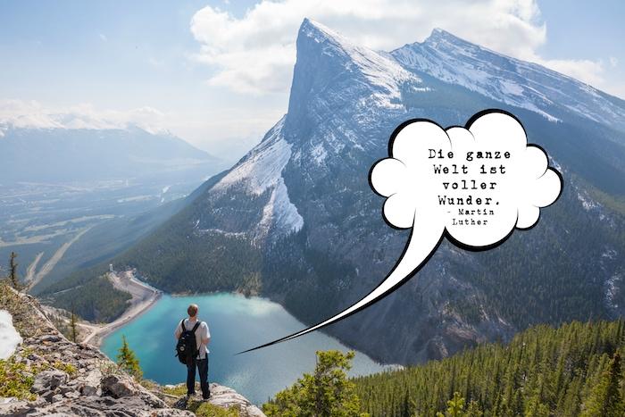 ein kurzer spruch von mrtin luther und ein bild mit bergen, see und einem reisenden mann