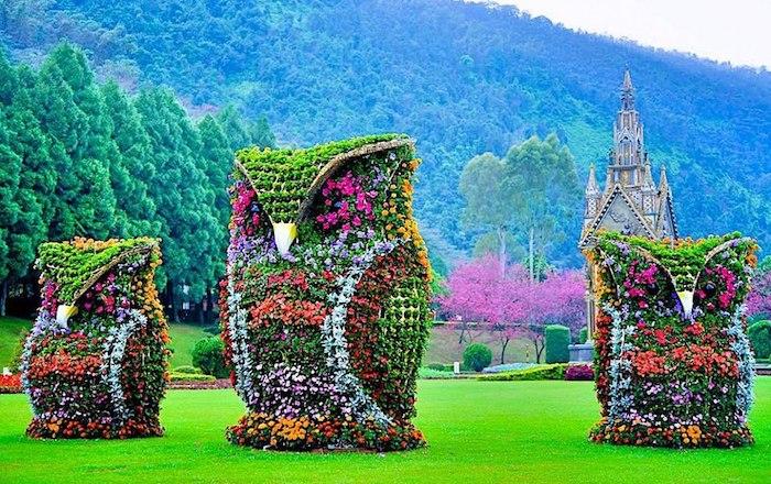 Streetart mit Blumen, große Bäume, Gebirge, Rasen, Eulen mit großen Augen