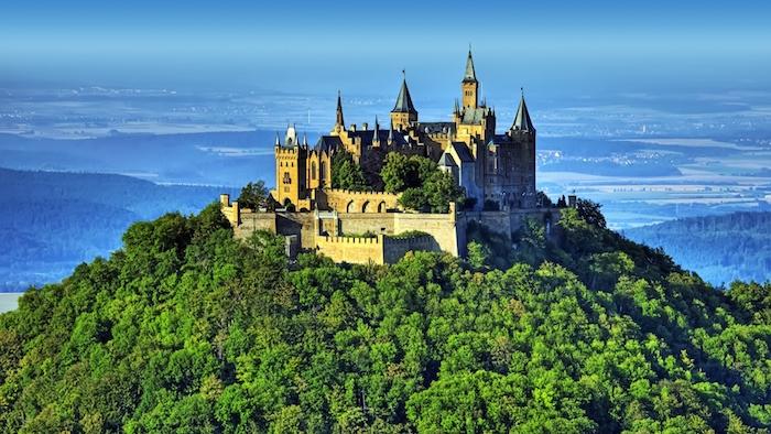 grüne Insel, Stadtaussicht, riesiger Burg auf einem Gipfel, blauer Hintergrund
