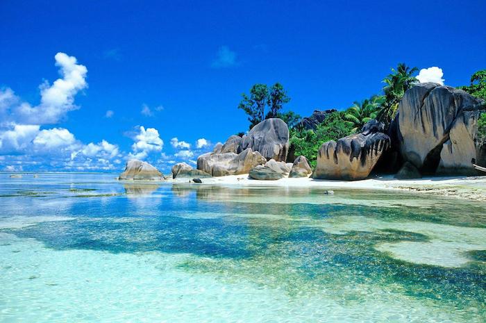exotischer Ort neben dem Ozean, Strand mit Palmen und großen Felsen