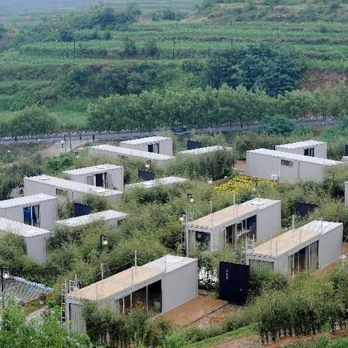 hier zeigen wir ihnen einige weiße kleine häuser, die aus alten cintainern gebaut wurden - mit einem großen grünen garten