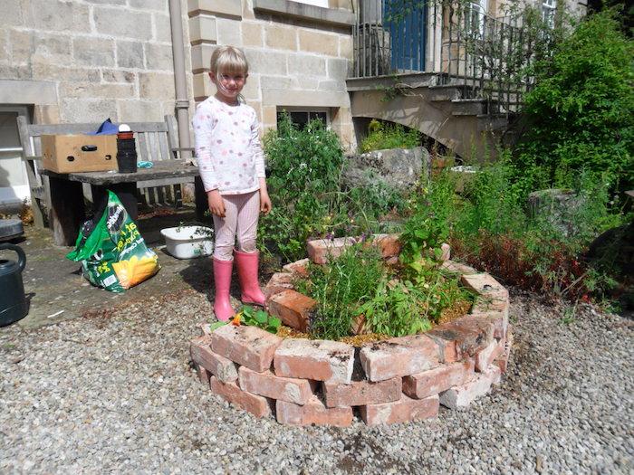 und jetzt zeigen wir ihnen ein inspirierendes bild mit einem tollen bild mit einem kleinen mädchen und kräuterspirale mit steinen und grünen kleinen 0flanzen und kräutern