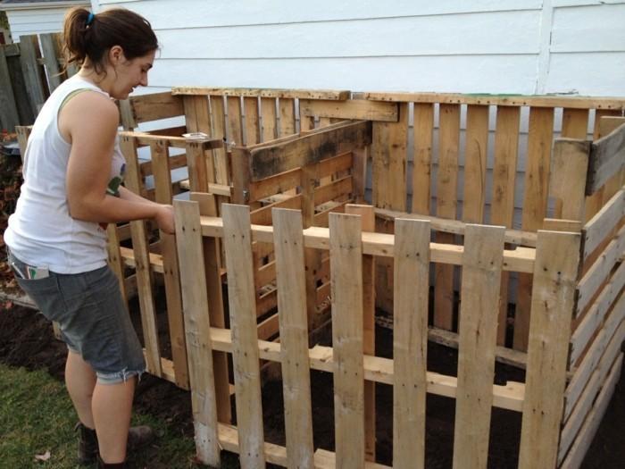 zum thema garten gestaltung - hier ist ein bild mit einer jungen frau und ihrem großen selbstgebauten komposter aus paletten