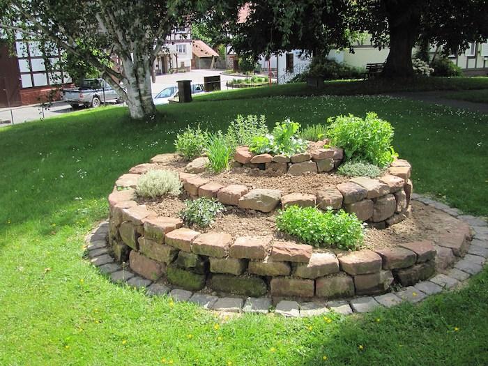 eine unserer ideen zum thema gartengestaltung - hier ist eine kräuterspirale mit steinen und verschiedenen kleinen grünen kräutern und pflanzen