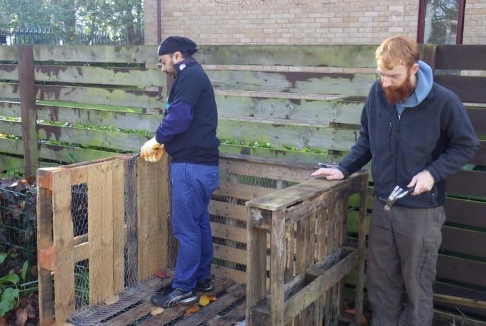 hier sind zwei männer, die einen großen komposter . aus den alten europaletten selber bauen - eine tolle idee zum thema gartengestaltung, die ihnen sehr gut gefallen kann