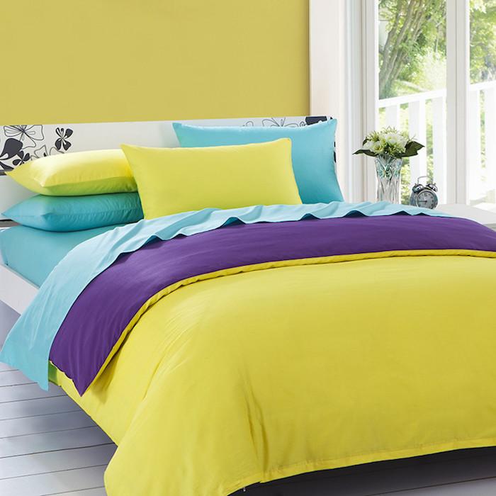 ein Doppelbett in Weiß mit Blumendeko auf dem Kopfbrett, bunte Bettwäsche, Blumendeko