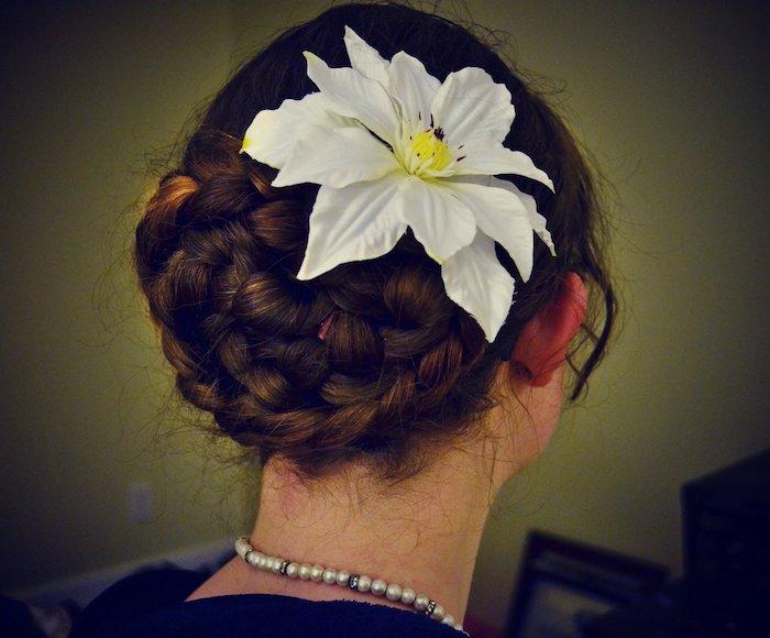 ein komplizierte geflochtene Oktoberfest Frisur mit einer weißen Blume