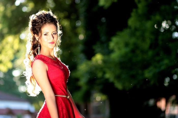 ein niedliches Mädchen in rotem Kleid mit dezentem Make up