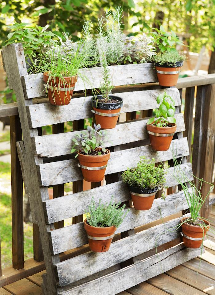 gartengestaltung beispiele, dekowand aus holz dekoriert mit blumentöpfen mit grünen pflanzen