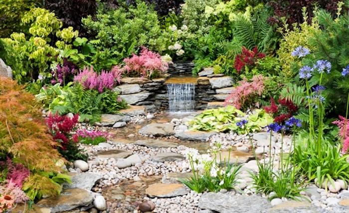 gartengestaltung ideen, kleiner wasserfall aus naturstein, viele gartenpflanzen