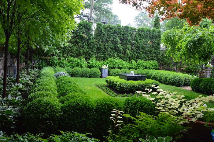 pflegeleichter garten, hintergarten mit vielen grünen büschen und fontäne im zentrum