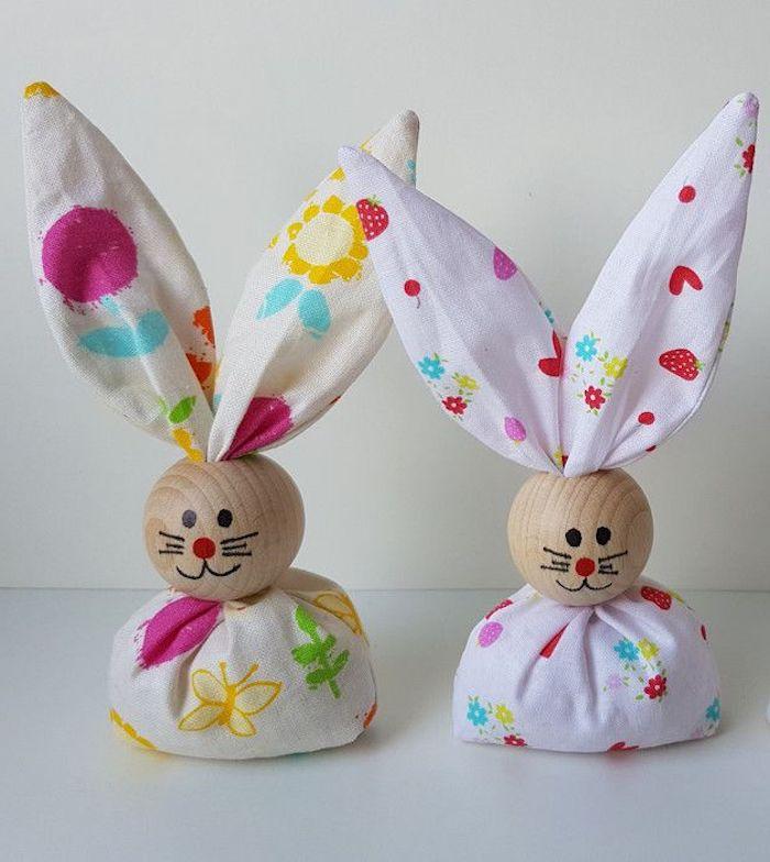 zwei kleine Hasen aus weißem Stoff mit Print, hölzerne Köpfe mit gemaltem Schnurrhaar