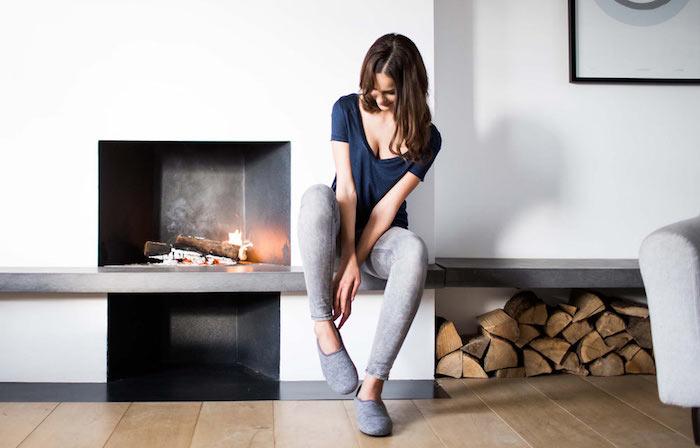 hochwertige hausschuhe, frau mit grauen jeans und dunkelblauem t-shirt