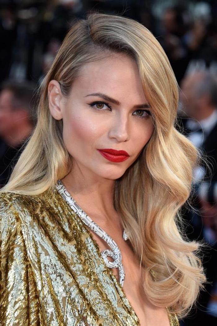 Haare blond färben, Blondton auswählen, lange gewellte Haare seitlich getragen, roter Lippenstift und schwarzer Lidstrich, goldenes Top, Kette in Form von Schlange