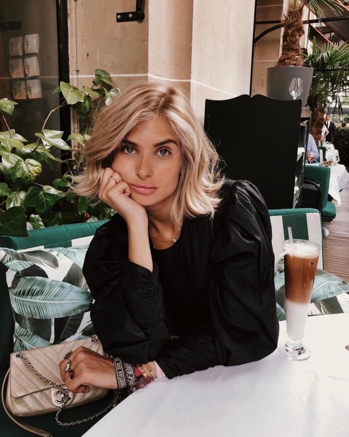 Blonde Haare, Bob Haarschnitt mit Seitenscheitel, schwarze Bluse mit weiten Ärmeln