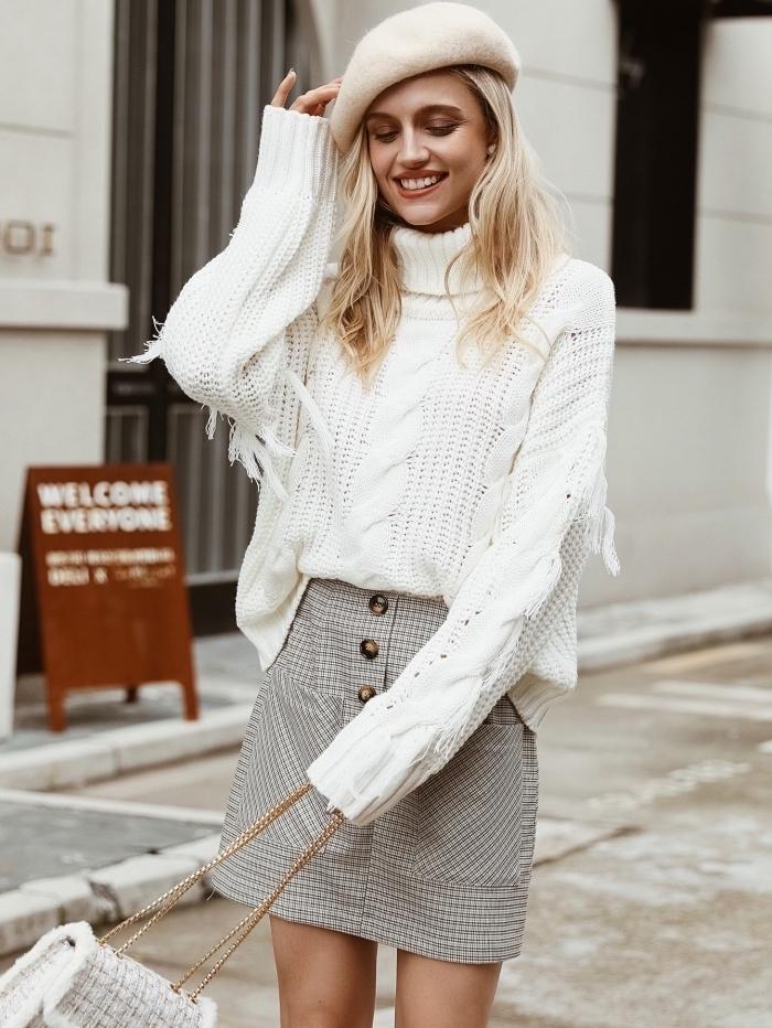 Blonde mittellange Haare, weißer Pullover und karierter Rock, weiße französische Mütze