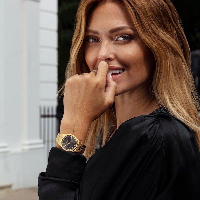 Goldblonde Haare, Smokey Eyes und matter Lippenstift, schwarzes Hemd, Armbanduhr mit goldener Kette, kleines Tattoo am Handgelenk
