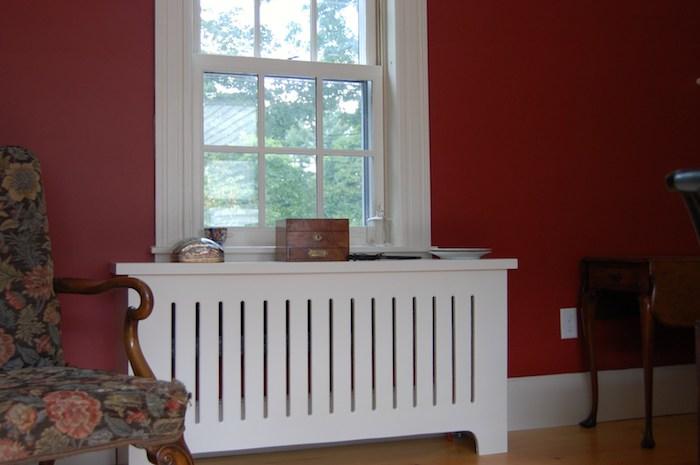 weiße Heizungsverkleidung im Kontrast mit den roten Wänden, bunter Sessel