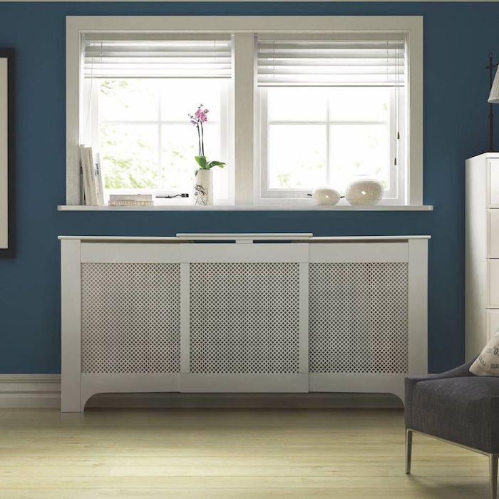 Heizungsverkleidung im Wohnzimmer in blau gestrichene Wände unter Fenster mit weißen Rahmen