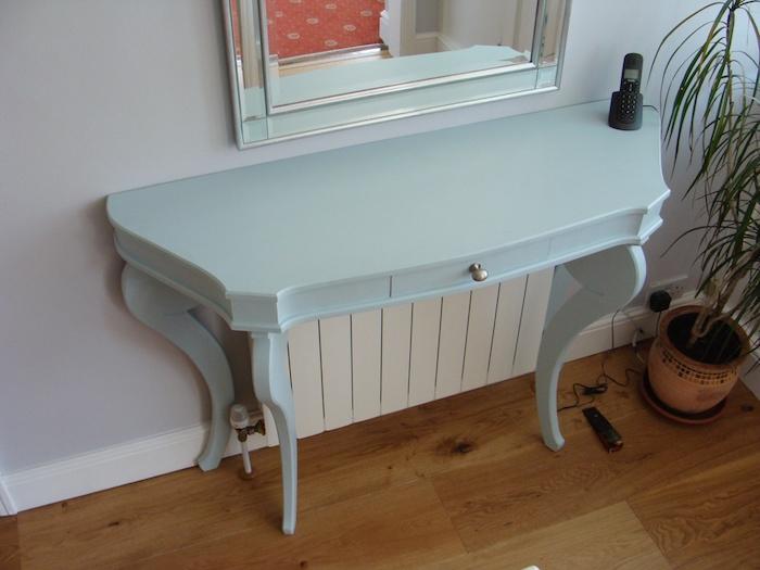 ein kleines blaues Tischlein, das die Heizkörper versteckt unter einem silbernen Spiegel