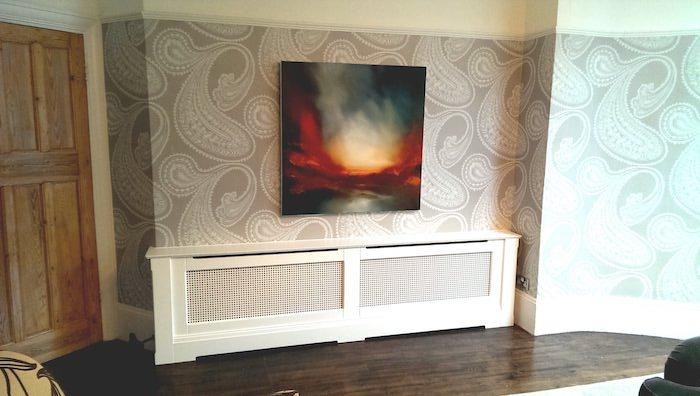 Heizkörperverkleidung in einem Wohnzimmer mit abstrakten Tapeten und mit einem abstrakten Bild