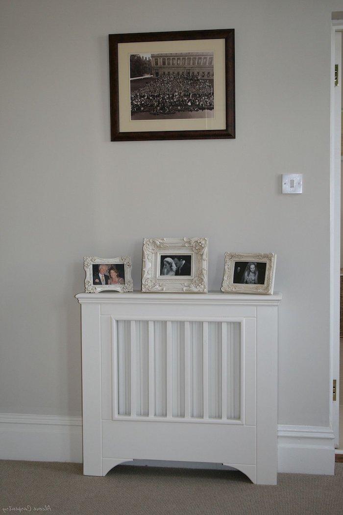weiße Heizung Abdeckung, die als ein moderner Kamin dient mit drei Bilder