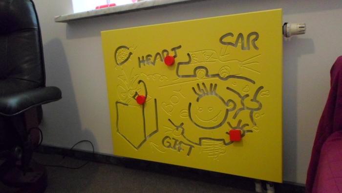 Heizkörperverkleidung im Kinderzimmer in gelber Farbe mit lustige Bilder für die Kleinen