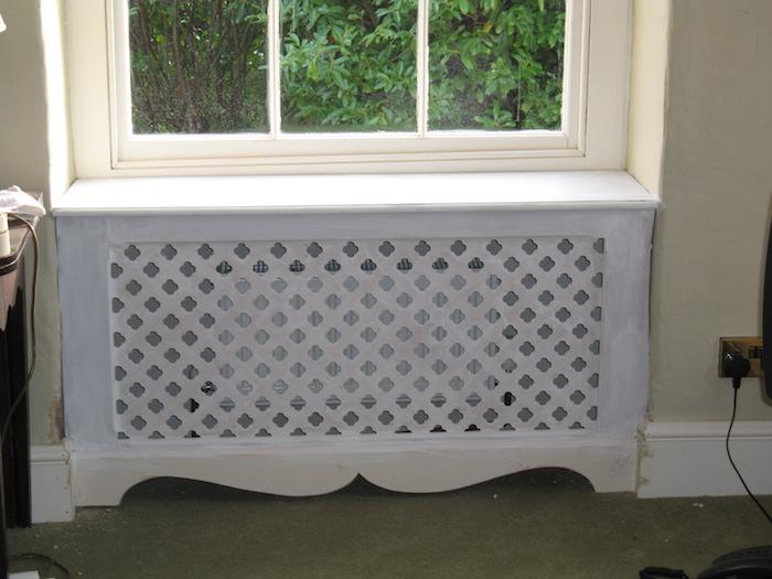 Heizung verkleiden mit einer weißen Abdeckung unter dem Fenster, das zu Garten sieht