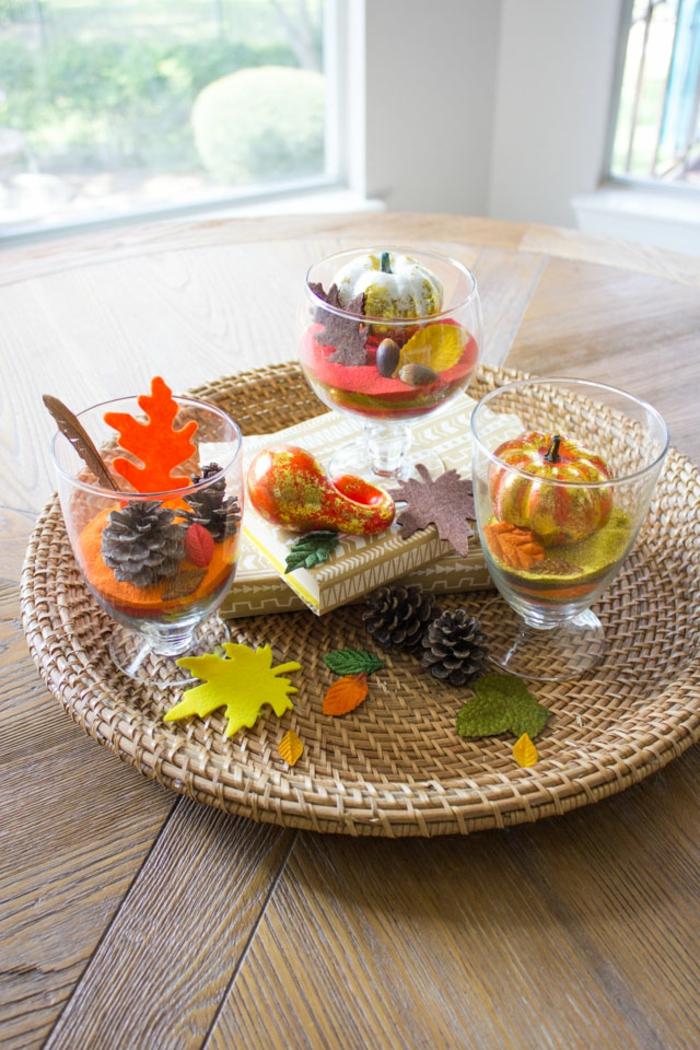 den Tisch herbstlich arrangieren, Teller aus Rattan, Zapfen und kleine Kürbisse in Bechern, herbstliche Nuancen