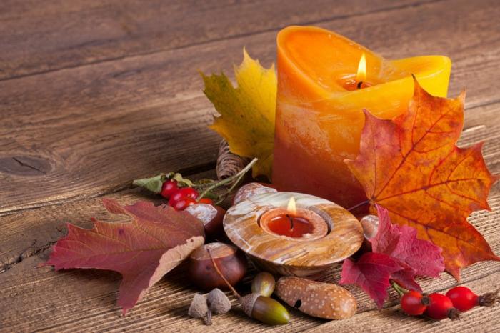 den Tisch herbstlich arrangieren, Kastanien, Eicheln, Herbstblätter und gelb-orange Kerze, herbstliche Nuancen