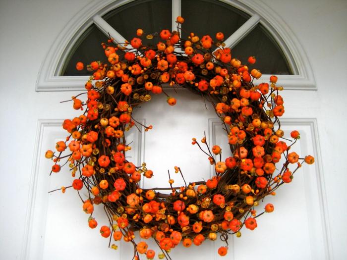 herbstlichen Kranz für die Eingangstür, kleine orange Kürbisse, die Farbe des Herbstes, Kontrast zur weißen Tür