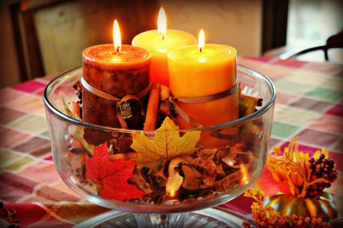 den Tisch herbstlich arrangieren, Kerzen in herbstlichen Nuancen und Herbstblätter in Glasschale