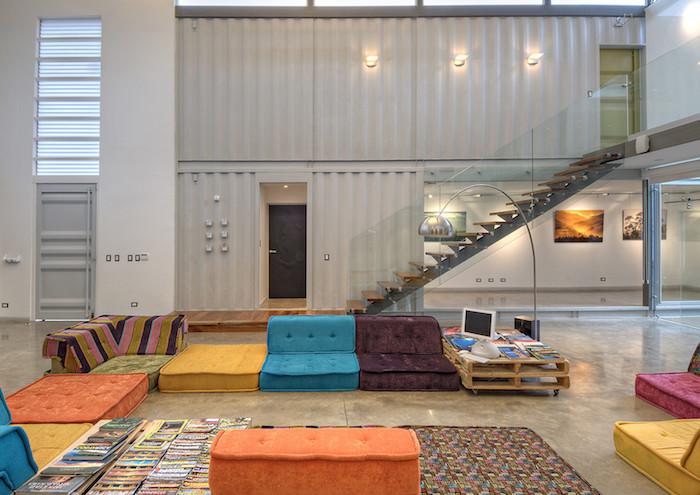 wir zeigen ihnen ein zimmer eines container hauses mit blauen, gelben und orangen sofas und teppich und lampen und treppe und wänden aus metall