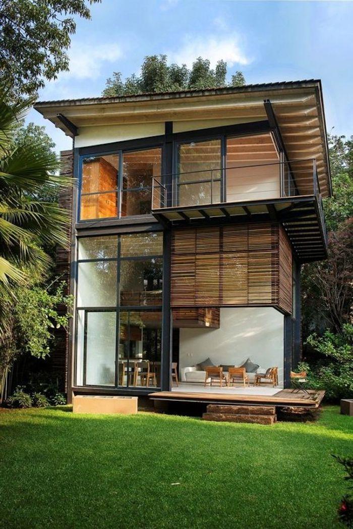 schönes zweistöckiges landhaus aus containern - mit einer terrasse, stühlen, tisch und einem garten mit palmen und grass