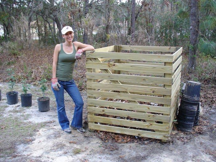 eine schöne junge frau und ein großer komposter azs holz - idee zum thema einen komposter selber bauen