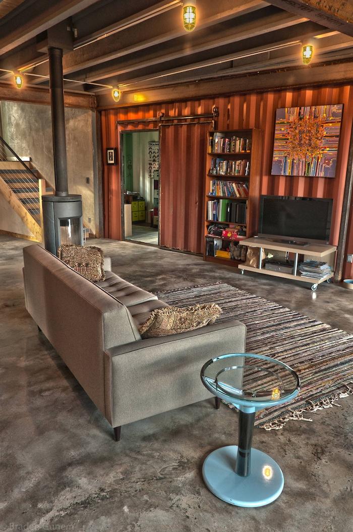 ein zimmer eines modernen container hauses mit lampen, sofas, tv, bildern und regalen