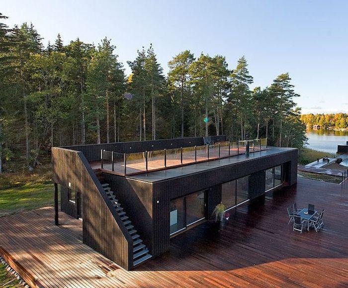 einstöckiges und sehr schön aussehendes landhaus aus holz und alten containern mit treppe und in der nähe von einem fluss