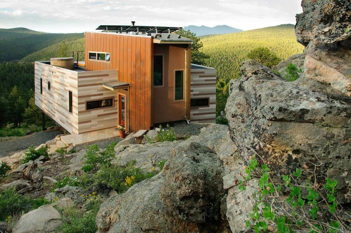 wir empfehlen ihnen einen blick auf diese idee für einen container haus aus holz zu werfen - ein landhaus, wald, grüne bäume und steine