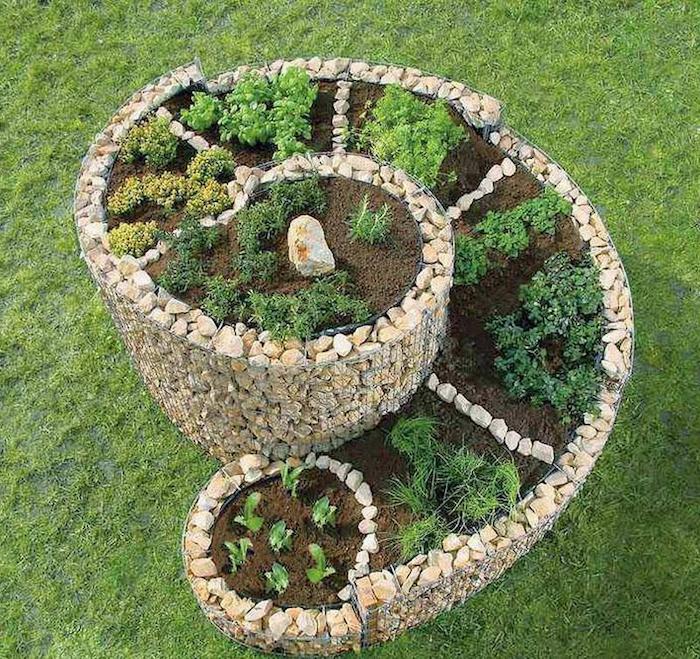 hier finden sie eine unserer ideen zum thema kräuterschnecke bauen - hier ist eine sehr schöne kräuterspirale mit kleinen grünen kräutern und verschiedenen pflanzen und kleinen weißen steinen