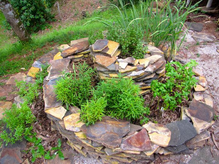 werfen sie einen blick auf diese idee für eine kräuterspirale selber bauen - hier ist eine kräuterspirale mit tollen grünen kräutern und verschiedenen pflanzen und steinen