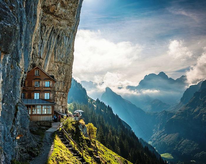 Berghaus mit atemberaubender Aussicht, spitze Berge, Sonnenstrahlen