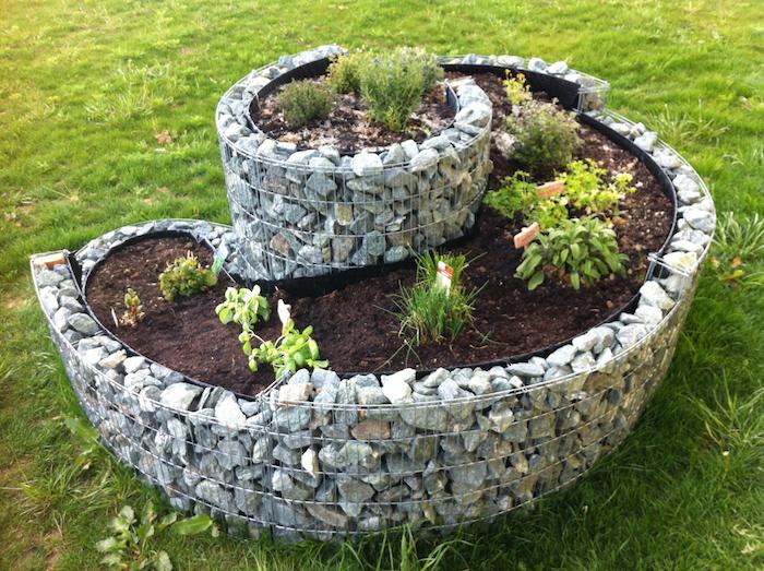 werfen sie einen blick auf diese idee zum thema kräuterspirale mit steinen und grünen pflanzen - idee zum thema gartengestaltung