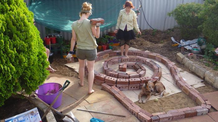 jetzt empfehlen wir ihnen einen blick auf diese idee zum thema kräuterspirale selber bauen zu werfen - ein bild mit einer kräuterspirale mit steinen und zwei jungen frauen