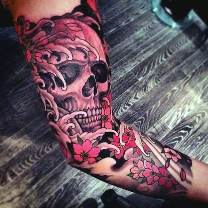 traditional tattoo am arm, tätowierung mit schädel-motiv und kirschenblüten