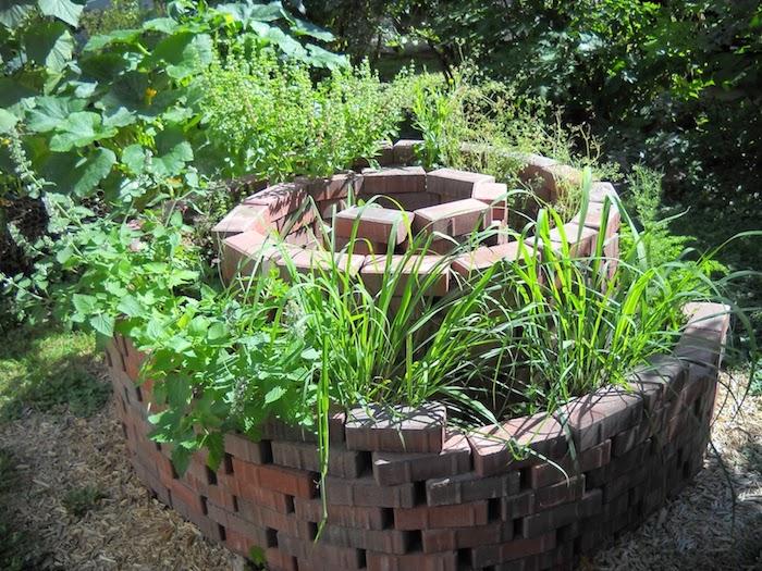 werfen sie einen blick auf diese idee für einen garten mit einer tollen schönen kleinen kräuterspirale mit steinen und grünen pflanzen