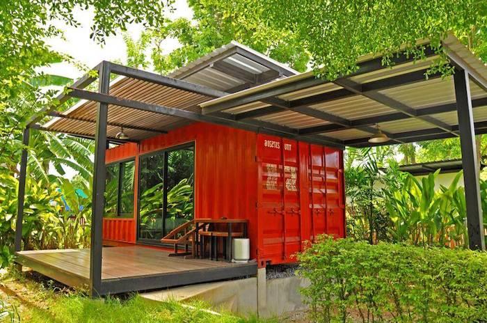 werfen sie einen blick auf diese idee für ein container haus - hier ist ein kleines rotes landhaus mit terrasse und sofas und einem garten mit grünen pflanzen und bäumen