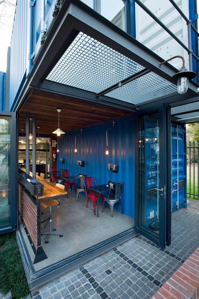 werfen sie ein blick auf dieses blaues container haus - mit blauen wänden, blauen stühlen, tisch und lampen