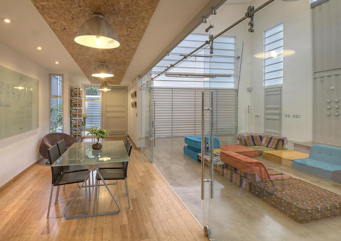wir empfehlen ihnen einen blick auf diese idee zum thema wohnen im container zu werfen - ein zimmer mit stühlen, tisch, lampen und gelben und blauen sofas